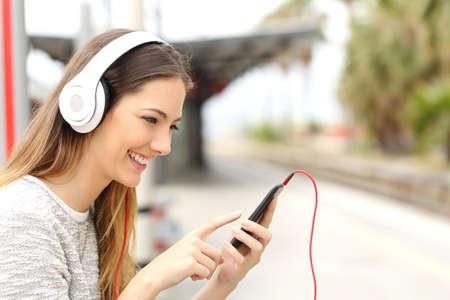 oir: Muchacha adolescente que escucha la música con los auriculares en una estación de tren, mientras que ella está esperando Foto de archivo