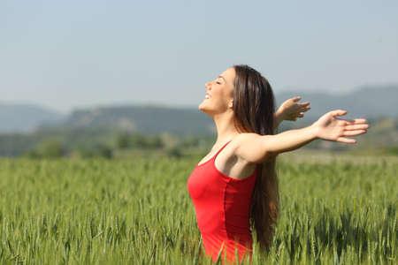 여자는 붉은 셔츠를 입고 녹색 밀 필드에 깊은 신선한 공기를 호흡 스톡 콘텐츠
