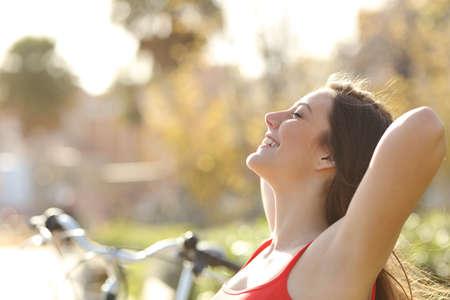persona respirando: Luz Detrás de una mujer respirando aire fresco y relajante en un parque en primavera o verano Foto de archivo