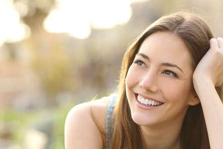 chicas sonriendo: Mujer con los dientes blancos pensando y mirando hacia los lados en un parque en verano