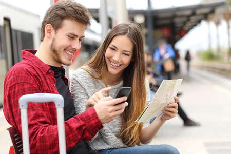 viagem: Turistas viajantes consultoria GPS e guia de um telefone inteligente em uma estação de trem