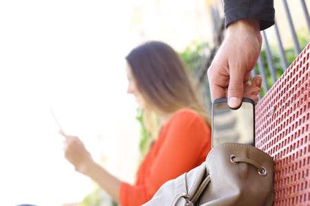 Dief het stelen van een mobiele telefoon naar een vrouw zitten op een bankje in een park Stockfoto