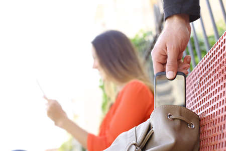 Thief stealing a mobile phone to a woman sitting on a bench in a park photo