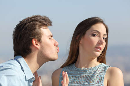 stressed woman: Friend zone concept with a man trying to kiss a woman and she rejecting him