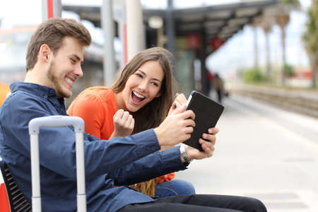 Euphoric couple watching movies or playing games in a tablet in a train station
