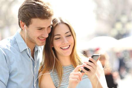 oir: Pareja feliz con auriculares que comparten música de un teléfono inteligente en la calle Foto de archivo