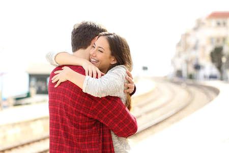 amigos abrazandose: Abrazos pareja feliz en una estación de tren después de la llegada