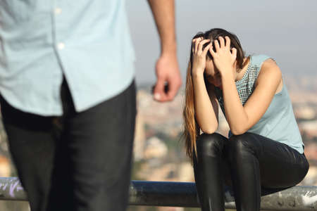 breaking up: Breakup of a couple with bad guy and sad girlfriend with a city in the background Stock Photo