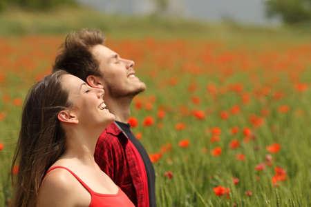 mujer meditando: Pareja feliz respirar aire fresco en un campo colorido con flores de color rojo amapola