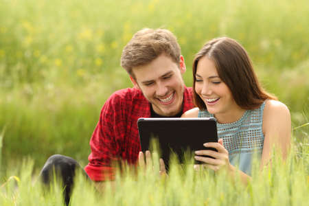 Funny couple watching and sharing videos in a tablet in a green field photo