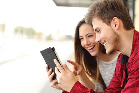 Happy couple watching videos or sharing media content from a tablet Stockfoto