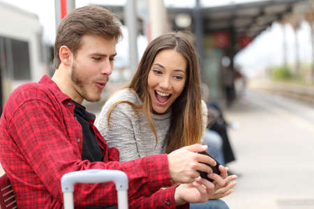 Funny couple playing games with a smart phone in a train station while they are waiting Stock Photo