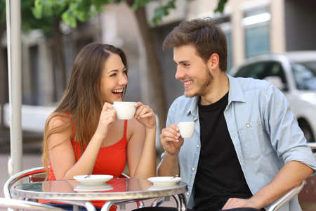 love at first sight: Happy couple or friends flirting talking and drinking in a restaurant terrace Stock Photo
