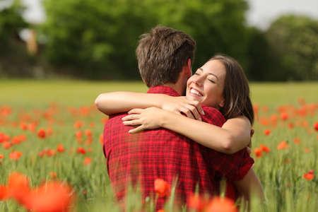 amigos abrazandose: Abrazos feliz pareja cariñosa después de la propuesta en un campo verde con flores rojas Foto de archivo