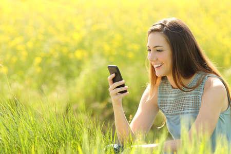 Vrouw met behulp van een slimme telefoon in een groen gebied met gele bloemen in de zomer Stockfoto