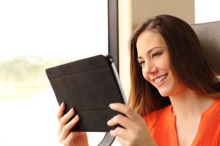 幸せな乗客女性のタブレットや電子ブックの電車の中を旅の読書
