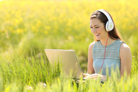 Woman working with a laptop and headphones in the middle of a a field in summer