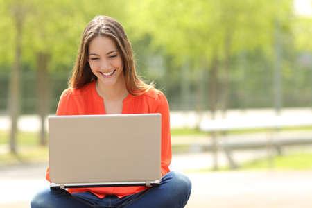 estudiantes: Vista frontal de una niña feliz estudiante que trabaja con un ordenador portátil en un parque verde de un campus universitario