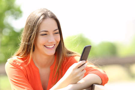 mobile device: Happy girl using a smart phone in summer in a park Stock Photo