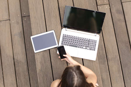 computer monitor: Woman using multiple devices phone laptop and tablet lying in a wood bench in a park
