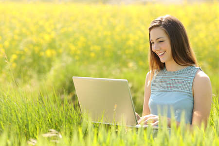Happy woman working with a laptop in a green field with yellow flowers Stockfoto