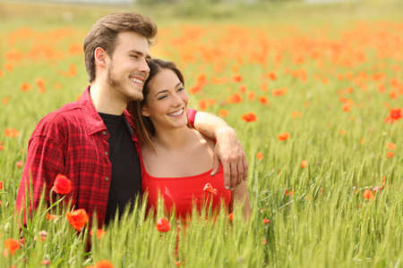 Couple hugging and walking in a green field with red flowers and watching forward