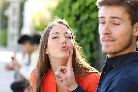 molesto: Mujer que intenta besar a un hombre y él está rechazando su aire libre en un parque Foto de archivo