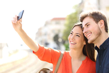 group travel: Traveler tourists couple photographing a selfie in a train station