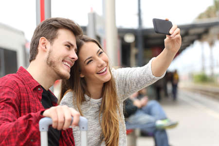season photos: Couple of travelers photographing a selfie with a smartphone in a train station Stock Photo