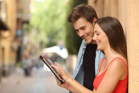 Profile of a happy couple browsing a tablet in the street photo