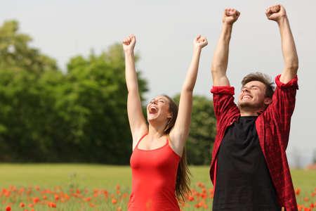 Euforisch gelukkig paar verhoging van de armen in een land veld met rode bloemen