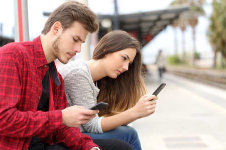 Teens obsessed with smart phones in a train station waiting for transport photo