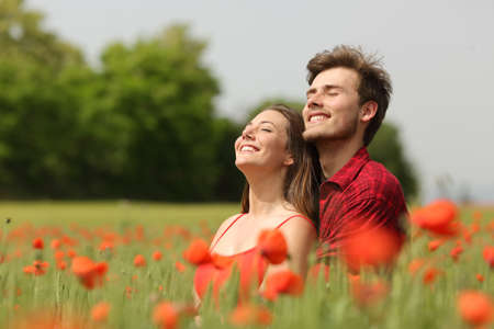 Romantic couple hugging and breathing fresh air in a warm field with red flowers