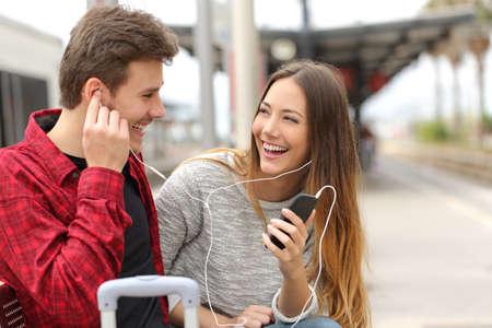 tren: Feliz pareja de viajeros que comparten m�sica vacaciones durante un viaje en una estaci�n de tren