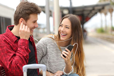 listening ear: Happy couple of travelers sharing music on holidays during a travel in a train station Stock Photo