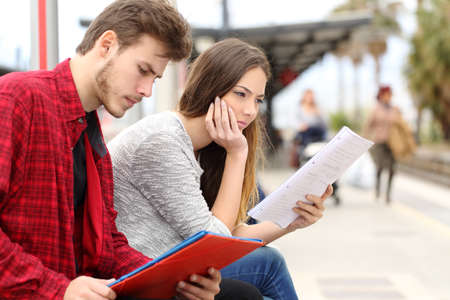 Two students studying concentrated while they are waiting transport in a train station photo