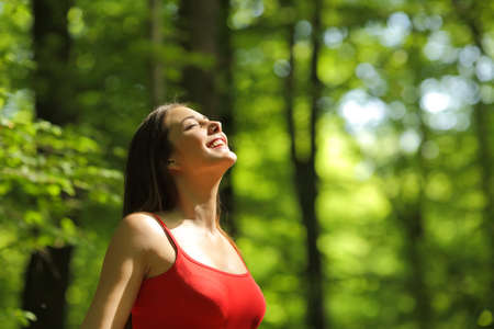 Woman breathing fresh air in a green forest in summer wearing a red shirt Stock Photo