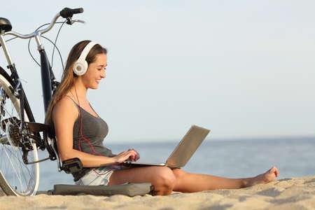 audifonos: Muchacha adolescente que estudia con un ordenador portátil en la playa apoyado en una bicicleta Foto de archivo