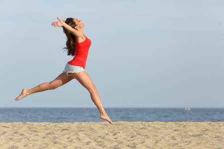 Side view, of a teen girl wearing red shirt and shorts jumping happy on the beach