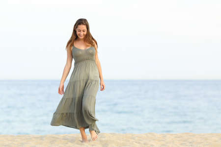 emotional freedom: Candid feminine dreamer girl walking enjoying carefree on the sand of the beach towards camera