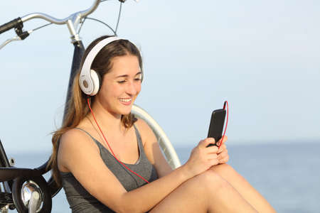 teens: Teen girl listening music from a smart phone sitting with a bike on the beach