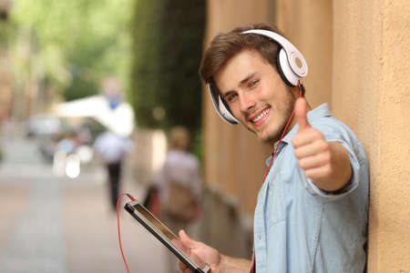 Happy man using a tablet with thumbs up in the street and looking at camera Stock Photo