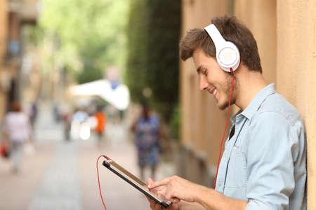 男の路上でヘッドフォンでタブレットを使用して、指で画面に触れて