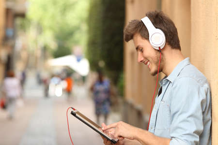 listening device: Profile of a man using a tablet with headphones on the street and touching the screen with the finger