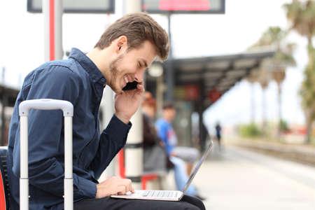 ラップトップと電話しながら駅で働くフリーランサーは輸送を待っています。