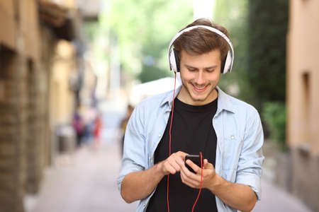 download music: Happy guy walking and using a smart phone to listen music with headphones