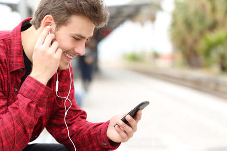 in ear: Hombre que escucha la m�sica con los auriculares de un tel�fono inteligente, mientras que est� esperando en una estaci�n de tren