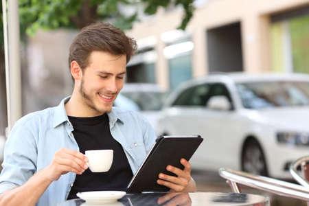 차 한 잔을 들고 커피 숍 테라스에서 전자 책 또는 태블릿을 읽는 행복한 사람