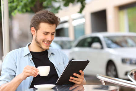Happy man reading an ebook or tablet in a coffee shop terrace holding a cup of tea