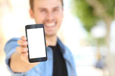 celulas humanas: Hombre Unfocused mano que muestra a usted una pantalla de teléfono en blanco en la calle